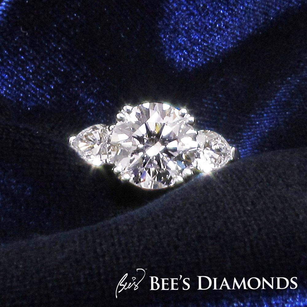 Round diamond with two pear shape diamonds on the side