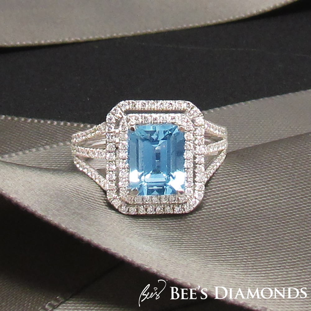 Aquamarine emerald cut ring with halos of small round diamonds